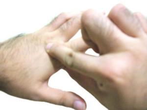 Ejemplo de un anclaje: Se toca la mano para asociar el estímulo con un estado interno, por ejemplo, seguridad en uno mismo.